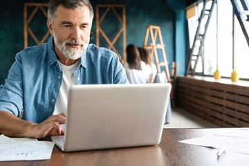 Cheerful mature man working on laptop and smiling while sitting at his working place