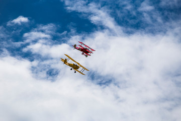 Aluminium Prints Dark grey Flying triplane and biplane replicas from world war I next to each other between the clouds.