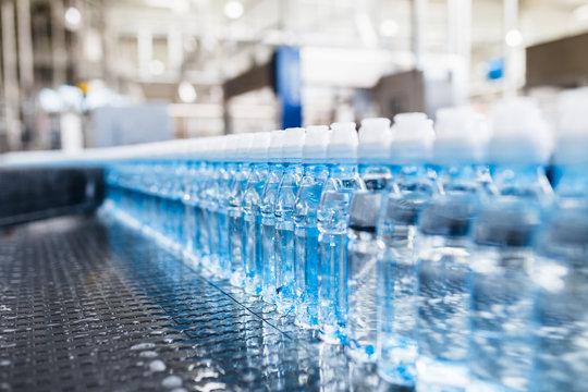 Bottling plant - Water bottling line for processing and bottling pure spring water into blue bottles. Selective focus.