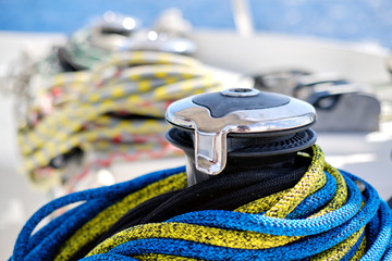 Winch with colourful yellow-blue rope on sailing boat,close up view, no people.