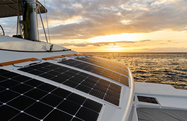 Solar powered catamaran at sunset, fully sustainable and powered by solar energy, charging batteries aboard a sailboat, vessel in ocean waters, nobody. Photovoltaic panels renewable eco energy concept