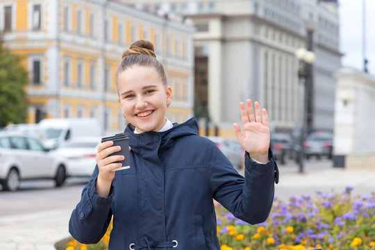 Good afternoon! Teenage girl shows a hello gesture or says goodbye and holds a cup of coffee in her hand.