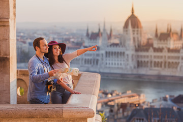 Young couple searching right direction on map from the point from Fisherman Bastion in Budapest with Hungarian Parliament building on background Fototapete