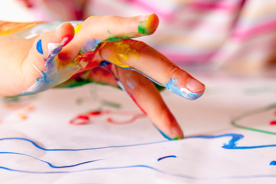 Close up young girl painting with colorful hands. Art,  creativity and painting concept.