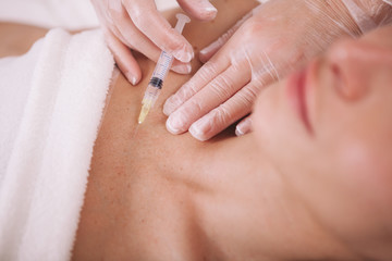 Cropped close up of a cosmetologist injecting filler fluid into chest skin of a female client. Woman getting skin rejuvenating injections by cosmetologist