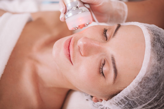 Close up of a beautiful woman receiving facial rf-lifting treatment by beautician. Rejuvenation, pampering concept