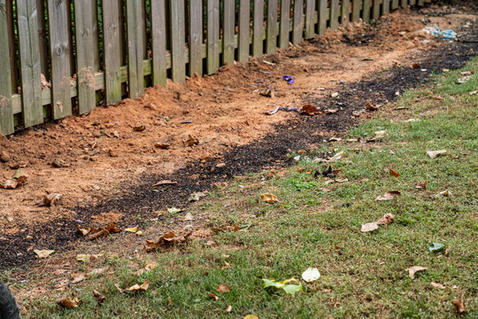 Dirt backfills this trench housing a French drain in a backyard DIY project to alleviate drainage issues