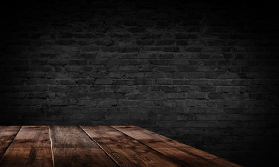 Wooden table, brick wall, ray of light. Empty scene of a dark room with old brick walls, neon light.