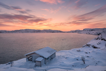 Foto auf Leinwand Rosa hell Wooden house and Barents sea at sunset in Teriberka, Murmansk Region, Kola Peninsula. Russia. It is not noise - Strong fog or smoke over sea. The sea is breathing in cold temperature. Focus on house