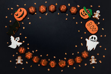 The hand-made eatable gingerbread Halloween inscription, pumpkin, ghosts, bat and sceletons on black background