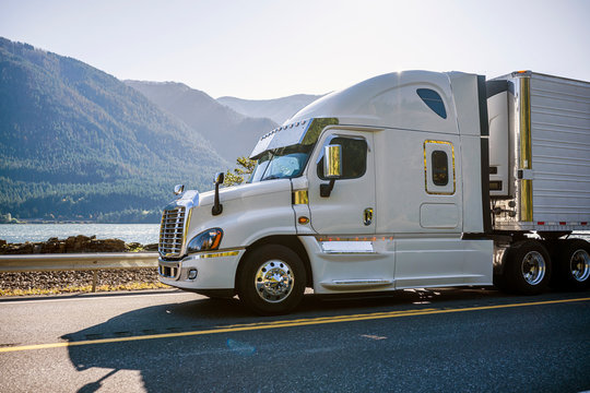 Big rig white semi truck with chrome accessories driving with reefer semi trailer for delivery commercial cargo on the road along the river