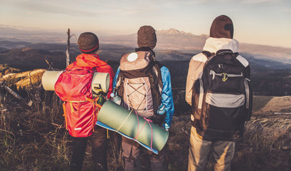 Group of young people admire the mountains. Three friends with backpacks and foam pads look at the mountain panorama. Cool autumn morning on the viewpoint. Soft colors and light noise.