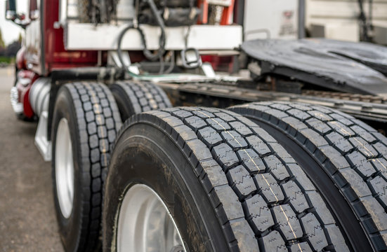 Wheels with tires on axels of big rig semi truck standing on parking lot
