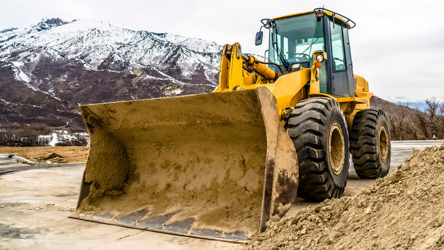 Panorama Front view of a yellow bulldozer against snow topped mountain and cloudy sky