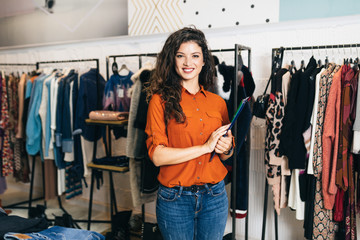 Beautiful female seller posing in exclusive boutique or store.