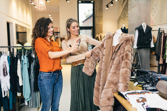Female seller taking photo of fur coat that her customer wants to buy.