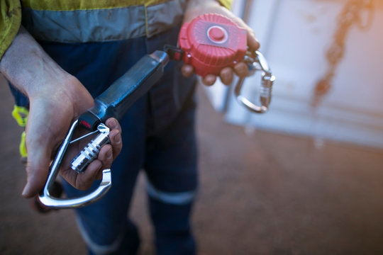 Male inspector hand testing opening locking carabiner gate which connecting with self retracting absorber safety device equipment ensure its working correctly as daily inspection prior to used
