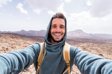 Handsome hiker taking a selfie hiking a mountain using his smartphone Wall mural