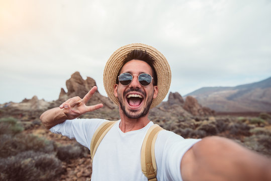 Handsome hiker taking a selfie hiking a mountain using his smartphone