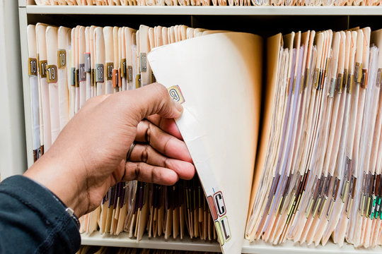 medical charts and records african american man sorting