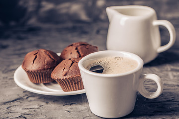 Wall Mural - Muffin with coffee on dark textured background.