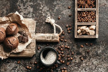 Wall Mural - Coffee beans with coffee and muffins on dark textured background.