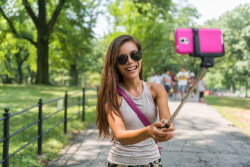 New York City tourist taking selfie stick photo in Central park, NYC. Happy travel Asian girl self-portrait picture with mobile phone at popular attraction walking in summer park in Manhattan, USA.