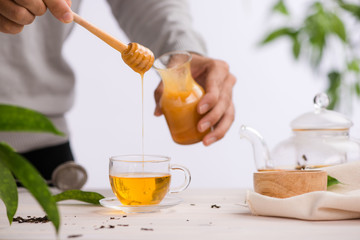 Cropped image of arista pouring honey into cup of tea