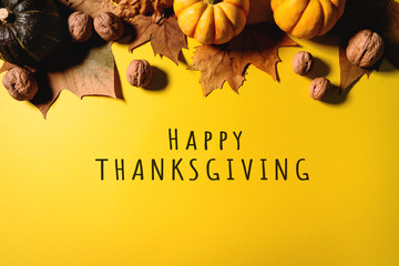 Happy Thanksgiving Day with maple leaves, nut and pumpkin on yellow background Wall mural