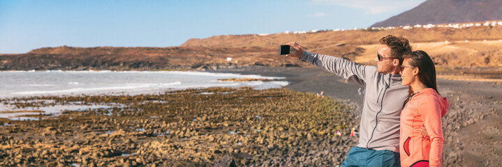 Selfie couple tourists taking photo at beach travel destination on summer vacation in the Canary Islands panorama. Woman and man traveling smiling to phone camera panoramic banner.