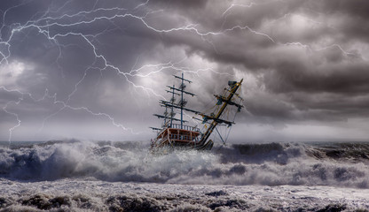 Tuinposter Schip Sailing old ship in storm sea against heavy sunset clouds