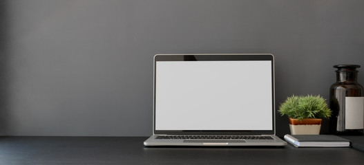 Open blank screen laptop computer in dark trendy workplace with copy space Wall mural