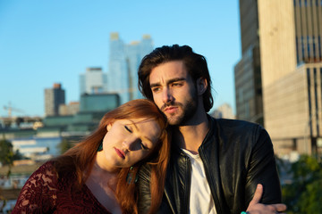 Couple looking wistful in urban setting with skyline in background