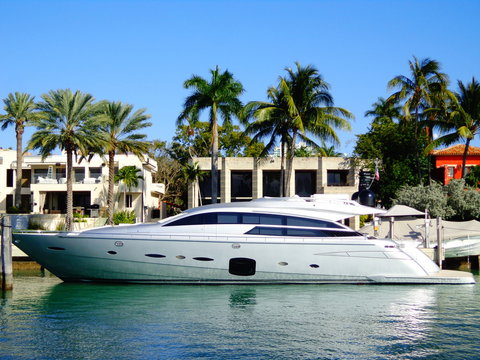 Life of Luxury: Ultra-modern silver yacht  in front of a millionaire's mansion in Miami, Florida (USA)
