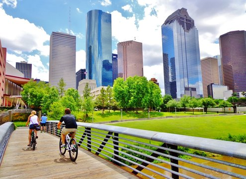 Bicyclists cross wooden bridge in Buffalo Bayou Park, with a beautiful view of downtown Houston (skyline / skyscrapers) in background on a summer day - Houston, Texas, USA