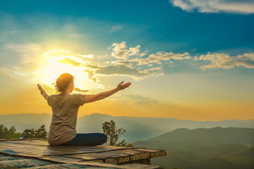 Healthy woman lifestyle balanced practicing meditate and zen energy yoga outdoors on the bridge in morning the mountain nature. Healthy life Concept.
