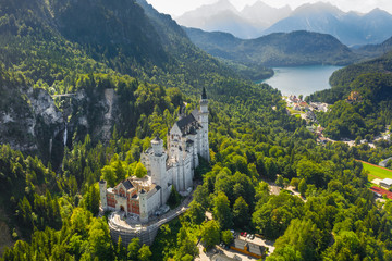 Aerial view on Neuschwanstein Castle Schwangau, Bavaria, Germany. Drone picture on Alpsee lake in Alps mountains.