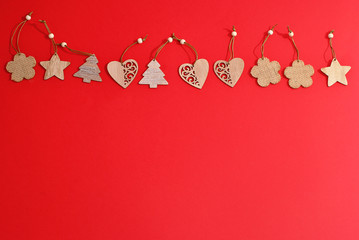 Christmas natural wood decorations on red paper  background with free copy space in the bottom Holiday winter handmade decoration garland on the top of picture Gift card design flat lay design