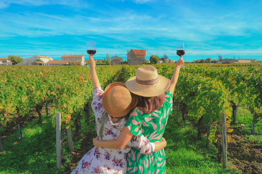 Back of yonug women drinking red wine at vineyard during thier vacation,  let's party concept