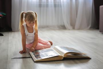 Caucasian child girl watching family photo album