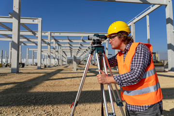 Mature Land Surveyor Looking Through Tacheometer on Construction Site