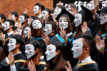 University students wearing Guy Fawkes masks pose for a photoshoot of a graduation ceremony to support anti-government protests at the Hong Kong Polytechnic University, in Hong Kong