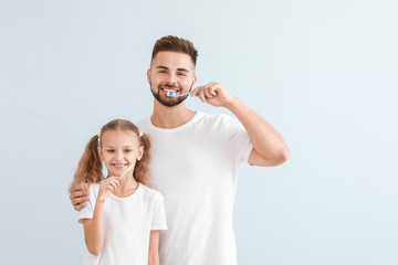 Fotomurales - Portrait of father and his little daughter brushing teeth on light background