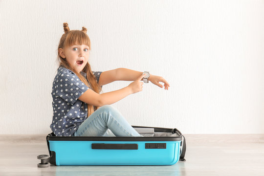 Surprised little girl sitting in suitcase and pointing on her wrist watch indoors