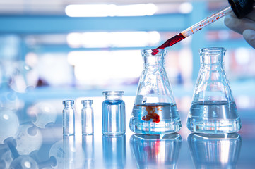 orange drop in glass flask with vial and chemical molecular on blue science laboratory background