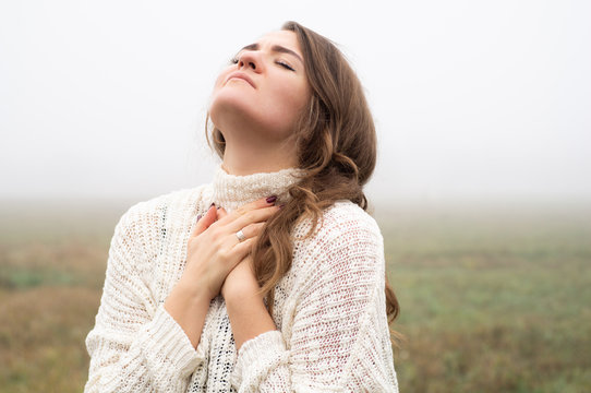 Girl closed her eyes, praying in a field during beautiful fog. Hands folded in prayer concept for faith