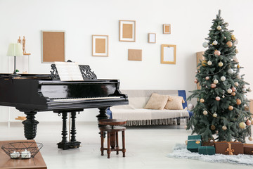 Grand piano with Christmas tree in interior of room