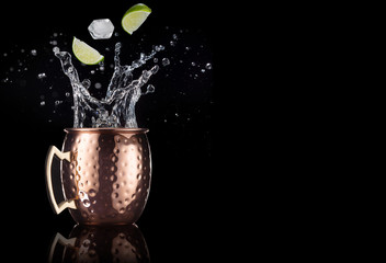 lime and ice falling into a splashing moscow mule cocktail isolated on black background