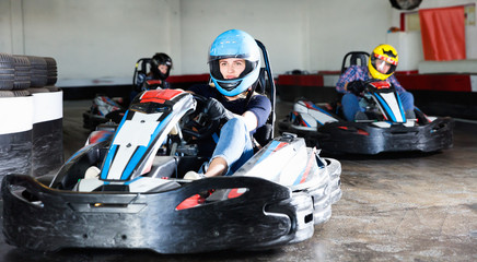 Group of people driving go-carts at racing track Wall mural