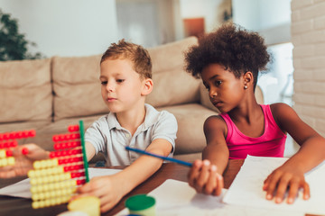 Multiracial children using abacus at home.